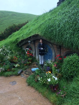 Gracie standing in front of a large Hobbit hole.